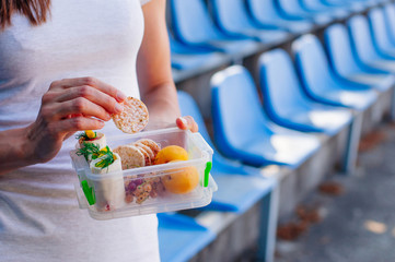 Close up of young woman eating from lunch box in stadium
