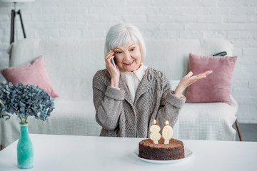 portrait of happy senior woman talking on smartphone while sitting at table with birthday cake at home