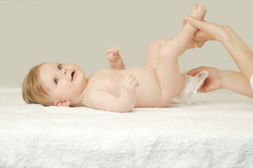 Newborn baby getting a diaper change: mom wiping baby's bottom with baby wipe
