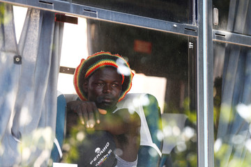 A migrant sits in a bus of Italian police after having been identified in a camp set by the Baobab aid group in Rome