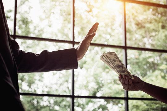Businessman refusing money, dollar bills - anti bribery and corruption concepts.