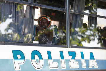 A migrant sits in a bus of the Italian police after having been identified in a camp set by the Baobab aid group in Rome