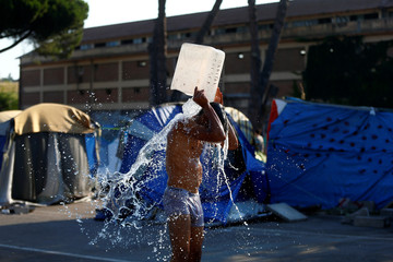 A migrant washes in a camp set by the Baobab aid group in Rome