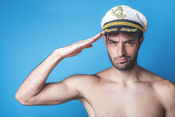 Attractive young sailor making a salutation gesture, blue background, studio image