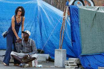 A migrants is helped as Italian Police identify migrants in a camp set by the Baobab aid group in Rome
