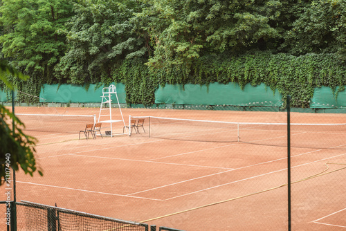 View Of Brown Tennis Court With Net, Chairs And Trees