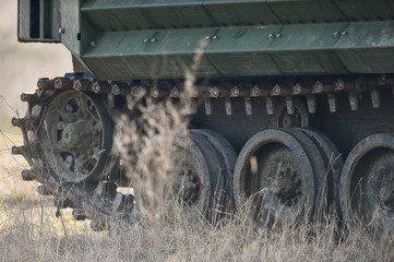 Amphibious tank caterpillars are seen on a field