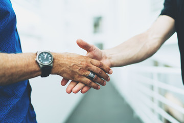 Closeup photo of two successful entrepreneurs shaking hands as a sign of productive partnership on a project. Professional marketing specialist received a job offer after applying for a job