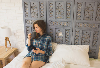 Beautiful girl is sitting on the white bed linen. Young woman in men's checkered shirt is drinking coffee and searching in social network on white pillow. Morning with black smartphone in hands.