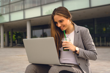 she is always on line. business woman using laptop and drink smoothie outdoor