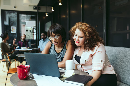 Businesswomen working on laptop while sitting in office