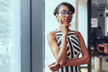 Portrait of young businesswoman standing near office window