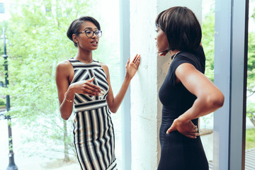Young businesswomen talking with each other at office