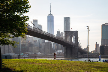 New York, City / USA - JUL 10 2018: Kid running on grass in Brooklyn Bridge Park in summer afternoon
