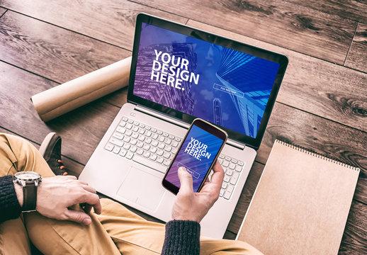 Laptop User Holding Smartphone Mockup