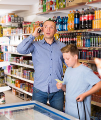 Man with phone  and son in food store