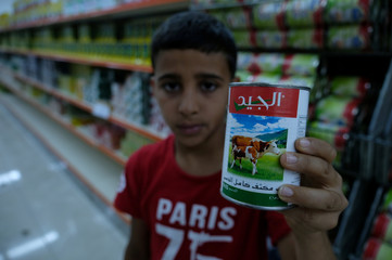 A boy carries a milk which he bought from the mall, in Benghazi