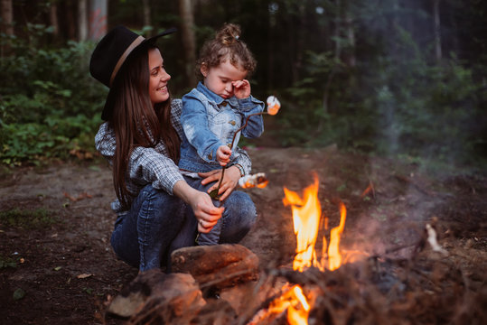 Mother and daughter fry marshmallow on  campfire in forest. Young family traveling active adventure vacations. Family camp.
