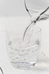 Pouring water from a glass jug into a glass. White wood background.