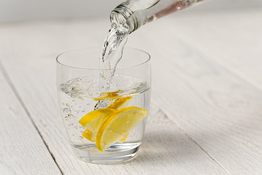 Pouring water from a glass bottle into a glass with lemon slices. White wood background.