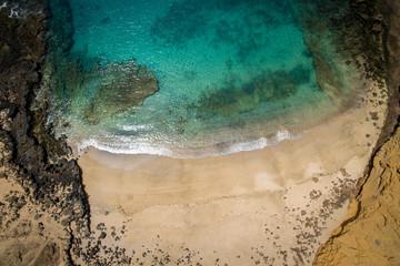 Ocean lagoon and sandy beach with rocks