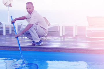 Pool cleaner during his work. Hotel staff worker cleaning the pool. Toning.
