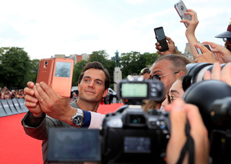 "Cast member Henry Cavill poses for pictures with cinema fans as he arrives for a photocall for the world premiere of the film ""Mission: Impossible - Fallout"" in Paris"