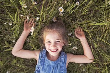 child on green daisy grass in a summer park sunset time