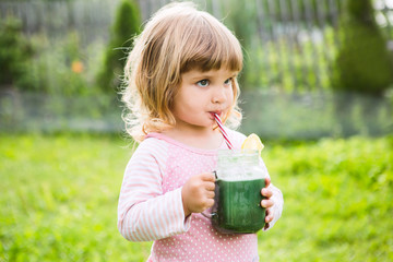 Cute little child drinks healthy green smoothie with straw in a jar mug against the background of greenery outdoor.  Wall mural