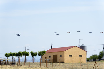 Three Boeing CH-47D Chinook helicopters flying in line with a Eurocopter Super Puma in front of the line