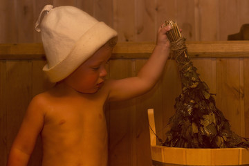 Beauty, healthcare. baby Boy relaxing in the sauna Toddler with broom and hat in russian sauna or bath