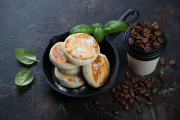 Curd pancakes or syrniki in a frying pan with a cup of takeaway coffee, horizontal shot on a dark brown stone background