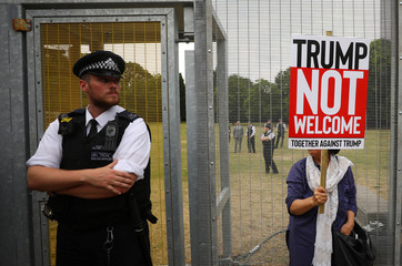 A demonstrator protests next to the specially erected fence surrounding the U.S. ambassador's residence, Winfield House, where U.S. President Donald Trump and the First Lady Melania Trump are staying, in London