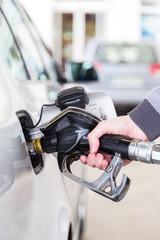 Pumping gas at gas pump. Closeup of man pumping gasoline fuel in car at gas station.