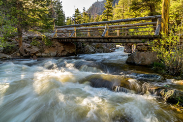 The Pool - A Spring evening view of rapid Big Thompson River rushing down under a wooden bridge at The Pool of Fern Lake Trail. Rocky Mountain National Park, Colorado, USA.