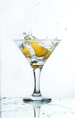 A glass of martini and slice of lemon, a splash and spray on a light background