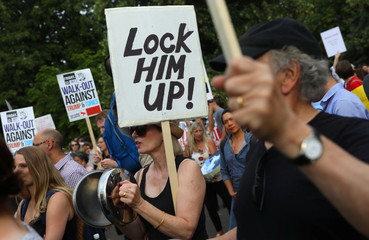 Demonstrators protest next to the specially erected fence surrounding the U.S. ambassador's residence, Winfield House, where U.S. President Donald Trump and the First Lady Melania Trump are staying, in London