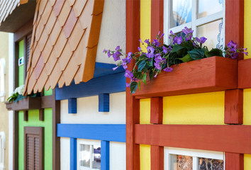 Wooden bench to relax under the window. Flowers at the window design of the children's town. Windows with curtains