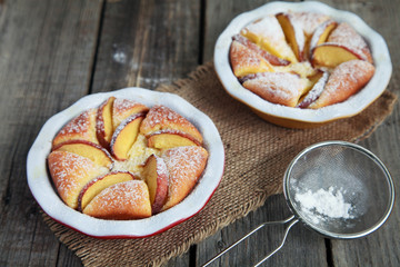 Homemade cottage cheese pie with peaches on wooden table with strainer and whisk