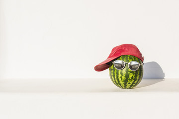 Creative and summer photography of watermelon in the form of a human head with glasses and red cap against a white wall background. Concept