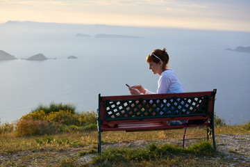 Young woman on a sunset background, the sea and mountains sits on a bench and looks at a smartphone