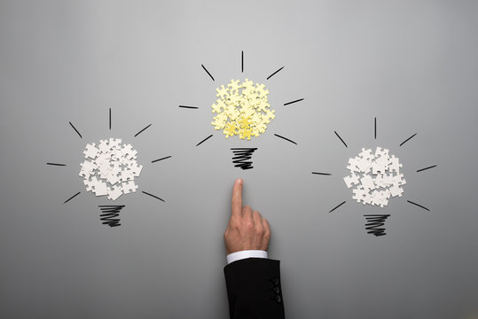 Three light bulbs made of scattered white and yellow puzzle pieces with a hand of a businessman