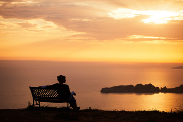 Young woman sits on a bench on a sunset background over the sea and mountains