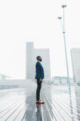 Side view of young businessman standing outdoors