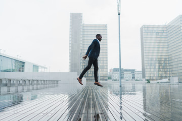 African-American male jumping on pavement in rain