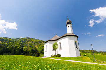 Chapel Sankt Anna in Achenkrich on a spring day with meadow of yellow flowers