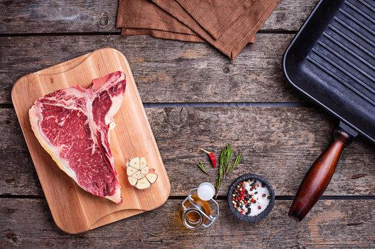 Raw T-bone steak and iron grill pan