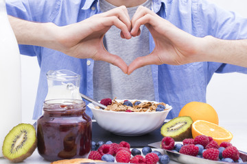 heart-shaped hands with breakfast and healthy food