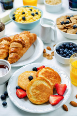 Breakfast table setting with flakes, juice, croissants, pancakes and fresh berries