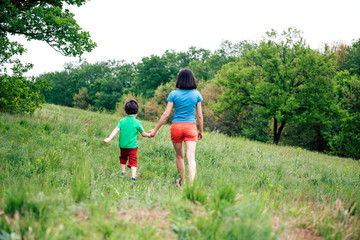 The boy walks with his mother in the meadow.